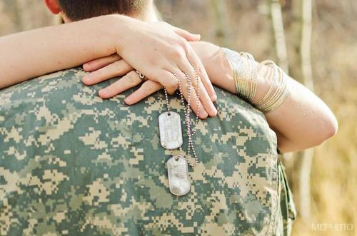 girlfriend's arms wrapped around soldier holding dog tags
