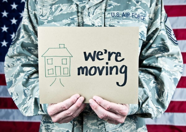 military service member holding we're moving sign