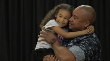 navy dad holding daughter