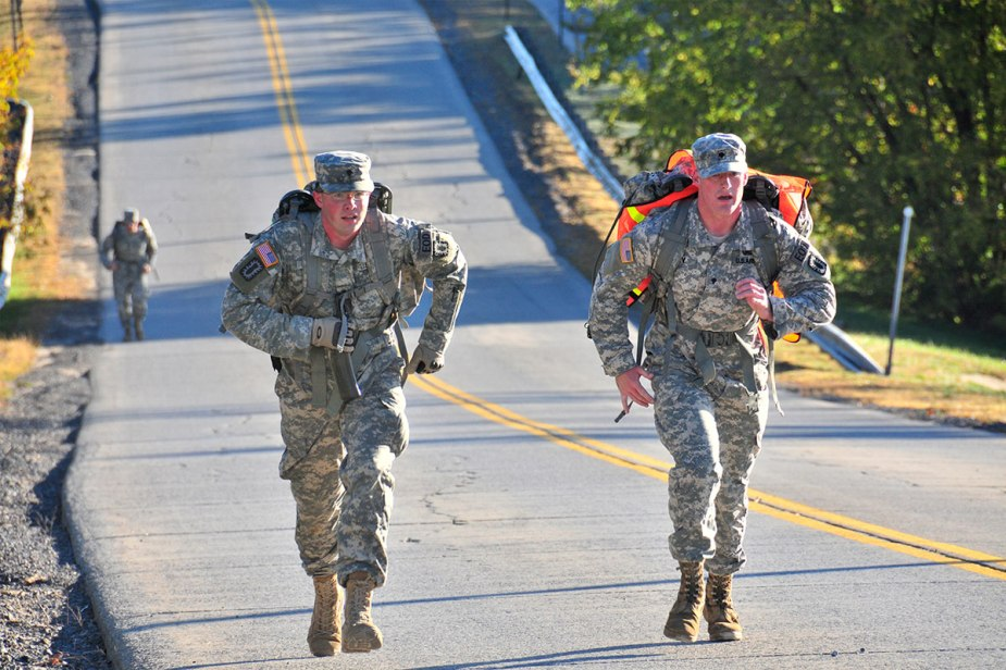 two army soldiers run up an incline with rucks