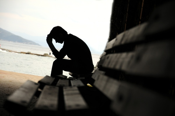 man seated on bench dealing with post traumatic stress disorder