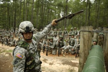 army drill sergeant with rifle at obstacle course