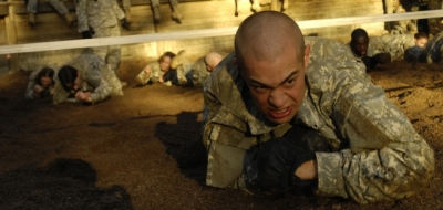 army recruit crawling through obstacle course